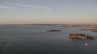 AX118_100 - 6K stock footage aerial video of Ellis Island and the Statue of Liberty at sunrise in New York