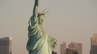 AX118_108 - 6K stock footage aerial video of closely orbiting the Statue of Liberty at sunrise in New York