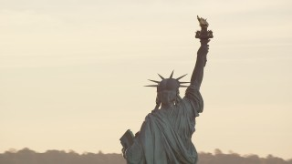 AX118_111 - 6K stock footage aerial video closely orbiting the Statue of Liberty with the rising sun overhead in New York