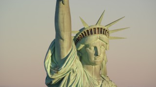 AX118_115E - 5.5K stock footage aerial video of orbiting the Statue of Liberty monument at sunrise in New York