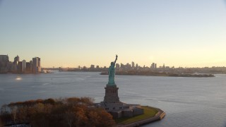 AX118_118 - 6K stock footage aerial video of flying away from the Statue of Liberty at sunrise in New York