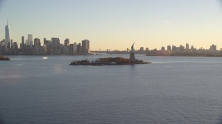 AX118_119E - 5.5K stock footage aerial video wide view of Statue of Liberty, and skylines of Brooklyn and Lower Manhattan at sunrise in New York
