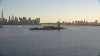 AX118_120 - 6K stock footage aerial video approach Statue of Liberty and Brooklyn and Lower Manhattan skylines at sunrise in New York