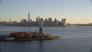 AX118_122 - 6K stock footage aerial video flyby Statue of Liberty for view of Lower Manhattan skyline at sunrise in New York