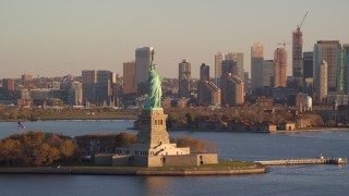 AX118_126 - 6K stock footage aerial video orbit Statue of Liberty, reveal Jersey City skyline at sunrise in New York