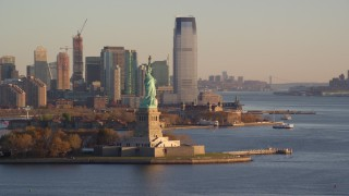 AX118_127 - 6K stock footage aerial video orbit Statue of Liberty and Jersey City skyline at sunrise in New York