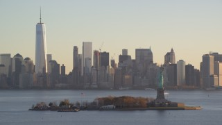 AX118_130 - 6K stock footage aerial video of a view of Statue of Liberty and Lower Manhattan skyline at sunrise in New York