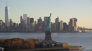 AX118_133 - 6K stock footage aerial video flyby Statue of Liberty to focus on Lower Manhattan skyline at sunrise in New York City