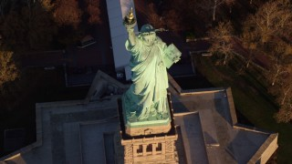 AX118_147 - 6K stock footage aerial video tilt to bird's eye view of the Statue of Liberty at sunrise in New York