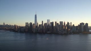 AX118_151 - 5.5K stock footage aerial video of approaching the Lower Manhattan skyline by the Hudson at sunrise in New York City