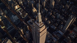 AX118_181E - 5.5K stock footage aerial video approach and tilt to bird's eye of the Empire State Building at sunrise in New York City