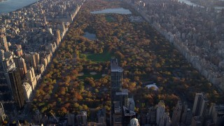 AX118_188 - 5.5K stock footage aerial video approach Central Park with Autumn leaves at sunrise in New York City