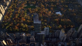 AX118_189 - 6K stock footage aerial video approach One57 skyscraper and Central Park with Autumn leaves at sunrise in New York City