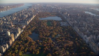 AX118_190 - 6K stock footage aerial video of flying over Central Park with Autumn leaves at sunrise in New York City