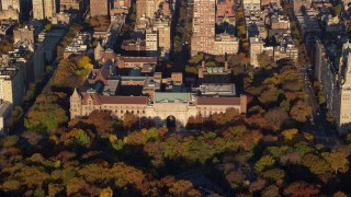 AX118_193 - 6K stock footage aerial video of orbiting the Museum of Natural History and trees with Autumn leaves at sunrise in New York City