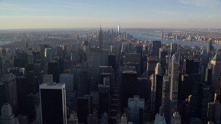 AX118_197E - 5.5K stock footage aerial video of Midtown skyscrapers at sunrise in New York City, with view of distant Lower Manhattan