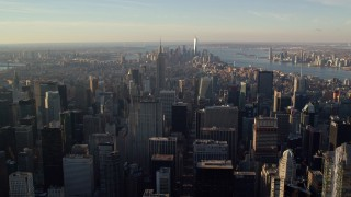 AX118_198 - 6K stock footage aerial video of a wide view of Midtown and Downtown skyscrapers at sunrise in New York City