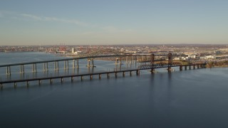 AX118_224 - 6K stock footage aerial video of flying by the Newark Bay Bridge and Lehigh Valley Bridge at sunrise in Newark, New Jersey
