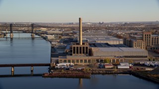 AX118_227 - 6K stock footage aerial video of riverfront factory at sunrise in Kearny, New Jersey