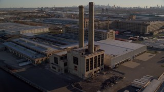 AX118_228 - 6K stock footage aerial video of orbiting a riverfront factory at sunrise in Kearny, New Jersey