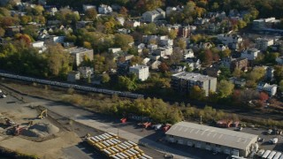 AX119_067 - 6K stock footage aerial video of tracking commuter train in Autumn, Yonkers, New York