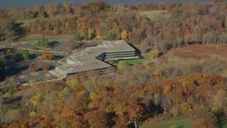 AX119_100 - 6K stock footage aerial video of an isolated office building in Autumn, Sleepy Hollow, New York