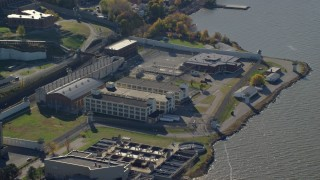 AX119_118 - 6K stock footage aerial video of orbiting riverfront Sing Sing Prison in Autumn, Ossining, New York
