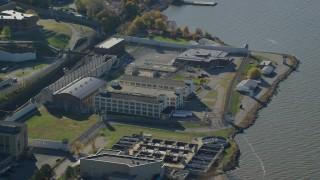 AX119_119 - 6K stock footage aerial video of an orbit of buildings at Sing Sing Prison in Autumn, Ossining, New York