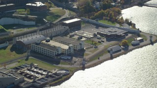 AX119_120 - 6K stock footage aerial video of circling Sing Sing Prison in Autumn, Ossining, New York