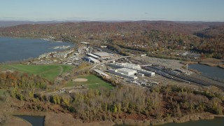 AX119_128 - 6K stock footage aerial video of approach riverfront rail station in Autumn, Croton on Hudson, New York