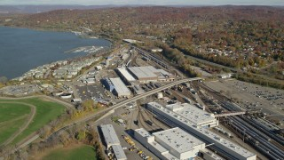 AX119_129 - 6K stock footage aerial video fly over a riverfront rail station in Autumn, Croton on Hudson, New York