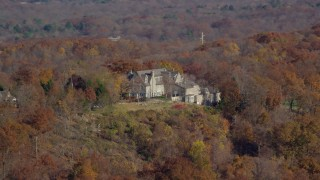 AX119_134 - 6K stock footage aerial video orbit an isolated hilltop mansion in Autumn, Croton on Hudson, New York