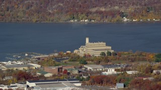 AX119_142 - 6K stock footage aerial video of a riverfront factory in Autumn, Peekskill, New York
