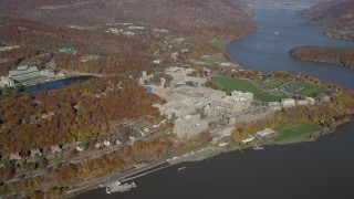 AX119_180E - 5.5K stock footage aerial video of a wide orbit around West Point Military Academy in Autumn, West Point, New York