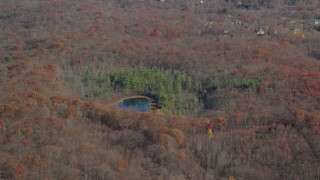 AX119_193 - 6K stock footage aerial video orbit small pond and forest in Autumn, Garrison, New York