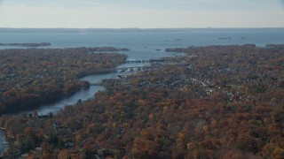 AX119_229 - 6K stock footage aerial video of a small town community and bridges over river in Autumn, Greenwich, Connecticut