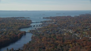 AX119_230 - 6K stock footage aerial video orbit small town community and bridges over river in Autumn, Greenwich, Connecticut