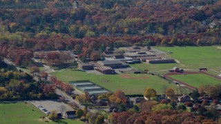 AX119_246 - 6K stock footage aerial video of a small time high school in Autumn, Syosset, New York