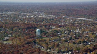AX119_247 - 6K stock footage aerial video of a water tower and suburban neighborhoods in Autumn, Syosset, New York