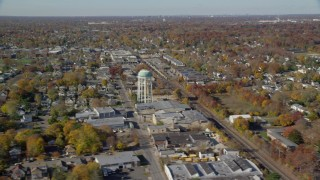 AX119_255 - 6K stock footage aerial video orbit industrial buildings and train tracks in Autumn, Farmingdale, New York
