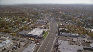 AX120_001 - 6K stock footage aerial video of warehouses on a wide street in Autumn, Farmingdale, New York