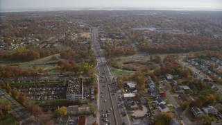 AX120_002 - 6K stock footage aerial video of homes, shops lining street near highway in Autumn, Farmingdale, New York