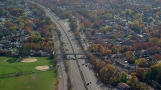 AX120_010 - 6K stock footage aerial video orbit light traffic on a freeway in Autumn, Seaford, New York