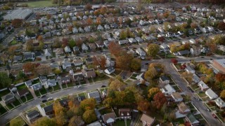 AX120_029 - 6K stock footage aerial video of flying over a quiet suburban neighborhood in Autumn, Hempstead, New York