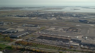 AX120_050E - 6K stock footage aerial video of flying toward John F. Kennedy International Airport in Autumn, in New York