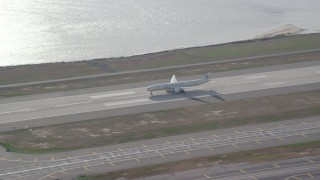 AX120_054 - 6K stock footage aerial video of an airliner cruising down runway at JFK Airport, New York