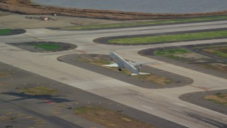 AX120_054E - 6K stock footage aerial video of an airliner cruising down runway at JFK Airport, New York
