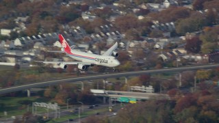 AX120_060E - 6K stock footage aerial video of a cargo plane descending toward JFK Airport, New York in Autumn