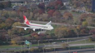 AX120_061 - 6K stock footage aerial video track cargo plane descending toward JFK Airport in Autumn