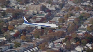 AX120_068 - 6K stock footage aerial video of a commercial jet approaching JFK Airport in Autumn